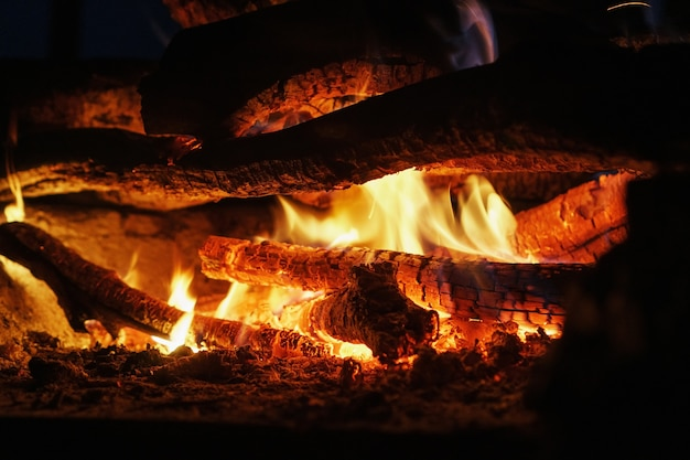 Bois dans un feu avec un feu ouvert et des charbons rouges dans l'obscurité