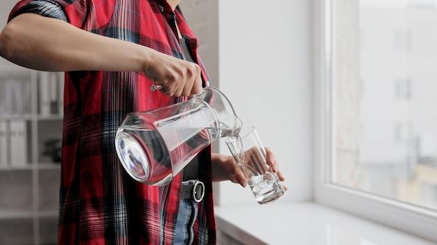 Bois de l'eau. la main d'une femme verse de l'eau fraîche et propre d'une cruche dans un verre. santé et beauté.