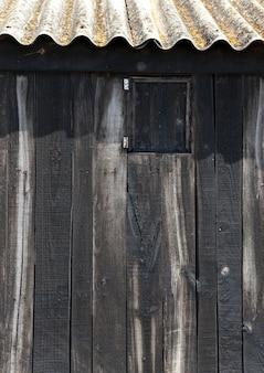 Bois noir vieilli avec toit ondulé à la plage des baléares