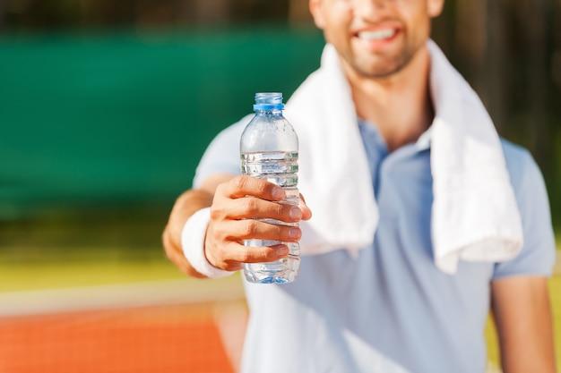 Bois un peu d'eau! gros plan d'un jeune homme heureux en polo et serviette sur les épaules étirant une bouteille d'eau en se tenant debout sur un court de tennis