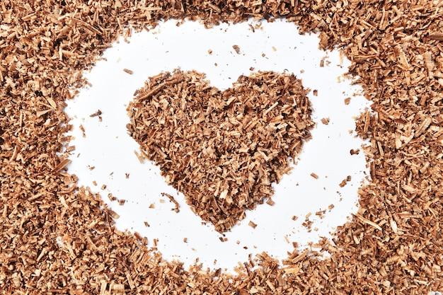Bois et poussière en forme de coeur sur fond blanc sale
