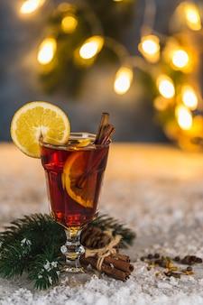 Boisson alcoolisée chaude au vin chaud avec des tranches de cannelle et d'orange sur le fond d'une guirlande de bokeh. fermer.