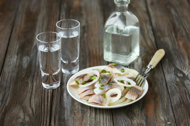 Boisson alcoolisée avec hareng salé et oignon sur mur en bois. boisson artisanale à base d'alcool et collation traditionnelle. espace négatif. célébrer la nourriture et délicieux.