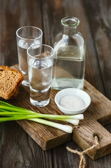 Boisson alcoolisée avec oignon vert, pain grillé et sel sur mur en bois. boisson artisanale à base d'alcool et collation traditionnelle. espace négatif. célébrer la nourriture et délicieux.