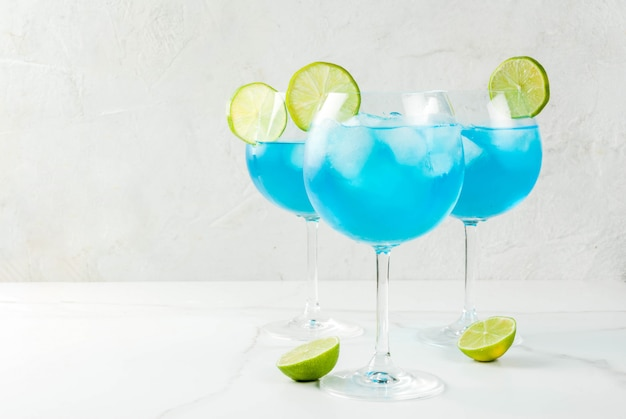 Boisson alcoolisée. verres avec un cocktail alcoolisé bleu avec de la glace et une garniture au citron vert. curaçao bleu. alcool.