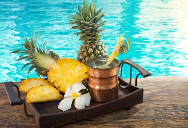 Boisson à l'ananas dans des verres avec des tranches d'ananas sur une feuille de palmier vert près de la piscine