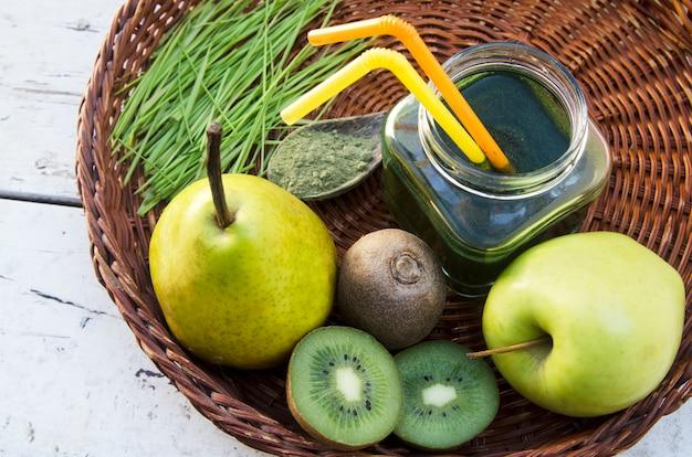 Boisson antioxydante à partir de fruits verts frais avec des pousses de blé et de la poudre à la cuillère sur une assiette en osier.