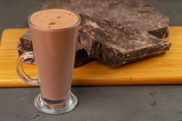 Boisson au cacao chaud dans une tasse en verre et barre de chocolat sur fond gris