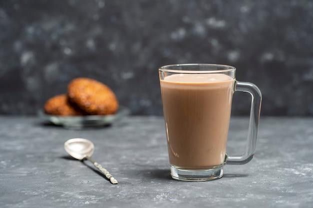 Boisson au cacao chaud dans une tasse en verre et biscuits à l'avoine sur la table grise. fermer