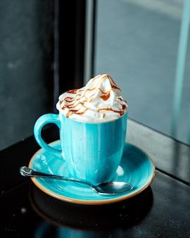 Boisson au café avec crème fouettée et sirop de caramel