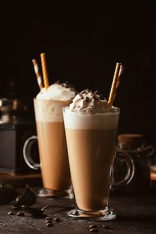 Boisson au café froid frappé ou frappuccino, avec de la crème fouettée et des pépites de chocolat, avec des pailles sur une surface sombre