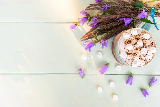 Boisson au café avec des guimauves et un bouquet de fleurs délicates