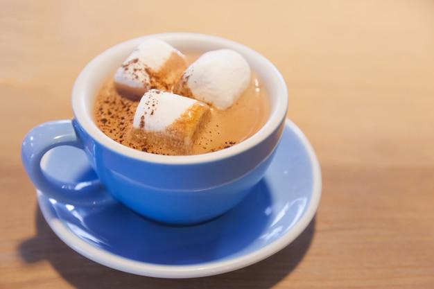 Boisson au chocolat chaud avec guimauve dans une tasse bleue sur table en bois