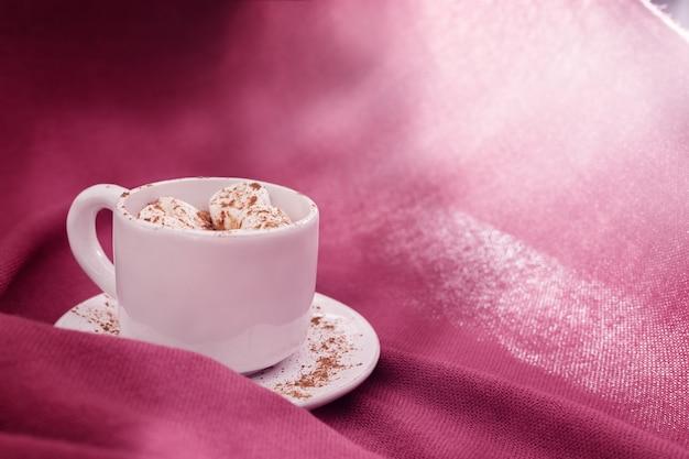 Boisson au chocolat chaud avec des guimauves dans une tasse blanche avec la lumière du soleil.