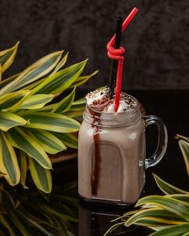 Boisson au chocolat dans un pot mason avec crème fouettée, arrose et sirop de chocolat sur le dessus