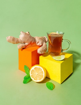Boisson au gingembre au citron dans une tasse en verre transparent. à côté se trouvent la racine de gingembre, la cardomome, la menthe et le citron vert.