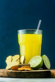 Boisson au gingembre et curcuma doré avec du jus de citron vert. boisson saine anti-inflammatoire de médecine naturelle et de naturopathie