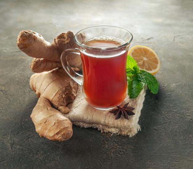 Boisson au gingembre dans une tasse en verre transparent. à côté se trouvent la racine de gingembre, la cardomome, la menthe et le citron.