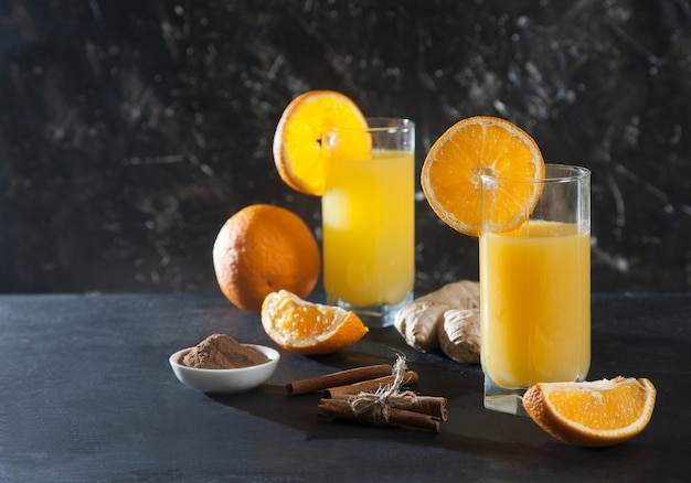 Boisson au gingembre et à l'orange dans des verres en verre, orange, gingembre et cannelle sur fond noir. détox. jus frais.