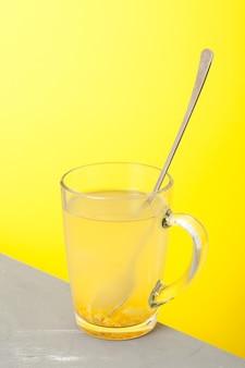 Boisson au miel et citron dans une tasse en verre avec cuillère