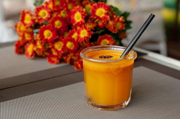 Boisson d'automne en verre avec tube et morceau d'anis étoilé sur fond de bouquet d'asters orange vif sur la terrasse extérieure. smoothie à l'argousier