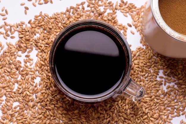 Une boisson aux céréales pour remplacer le café. tasse à café sur fond beige se bouchent