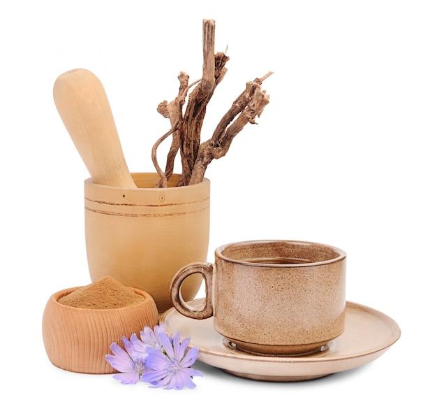 Boisson aux herbes de chicorée dans une tasse, chicorée broyée dans un bol en bois et racines de cichorium dans un mortier en bois
