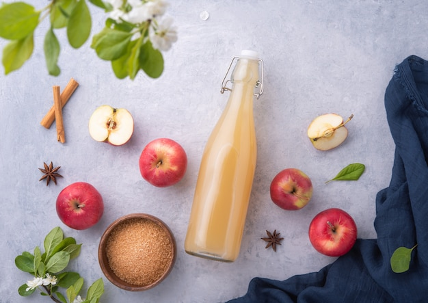 Boisson aux pommes fraîche faite maison avec de la cannelle et du sucre sur fond bleu.