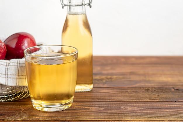 Boisson biologique saine. cidre de pomme dans un verre et pommes rouges fraîches.