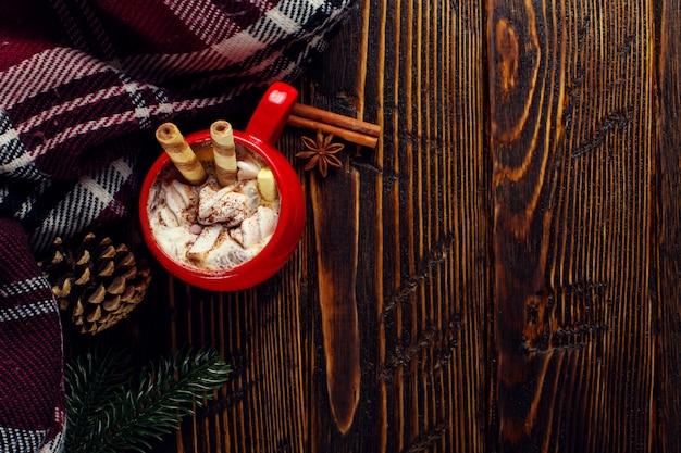 Boisson café en hiver, cacao à la crème fouettée et guimauves dans une tasse en céramique rouge