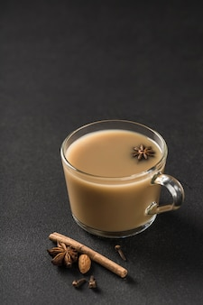 Boisson chaude asiatique populaire thé masala dans une tasse en verre transparent avec coriandre, cannelle et tige de rose sur fond noir.