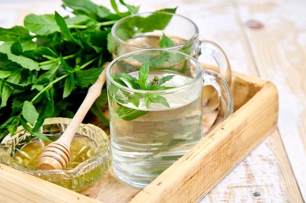Boisson chaude au thé à la menthe et aux herbes dans une tasse en verre