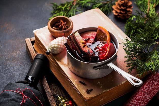 Boisson chaude au vin chaud avec agrumes, pomme, grenade et épices dans une casserole en aluminium avec des jouets d'arbre de noël vintage et branche de sapin sur une surface en béton