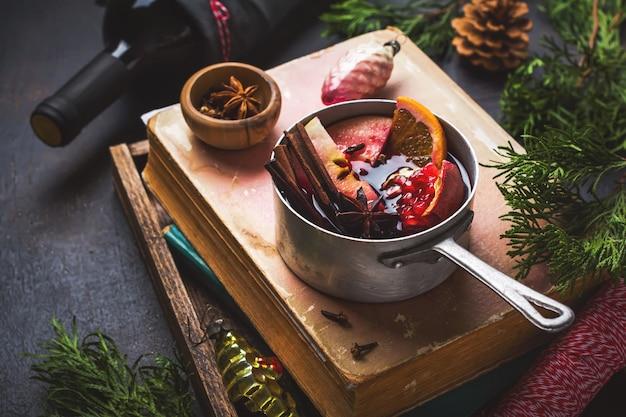 Boisson chaude au vin chaud aux agrumes, pomme, grenade et épices dans une cocotte en aluminium avec des jouets d'arbre de noël vintage et une branche de sapin sur une surface en béton. mise au point sélective.