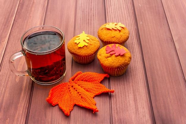 Boisson chaude d'automne. thé noir avec cupcakes, feuilles colorées