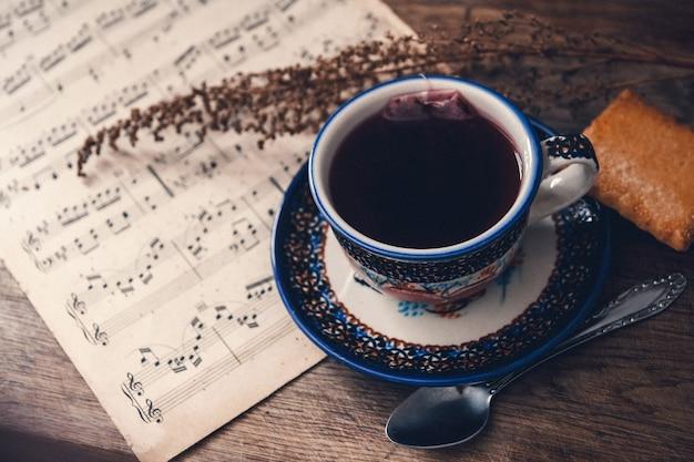 Boisson chaude et biscuit avec notes de musique et feuilles d'automne sur une surface de table en bois. vue de dessus.