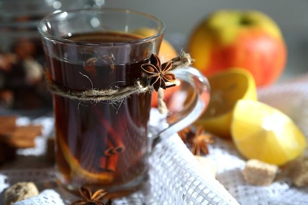 Boisson chaude dans une tasse en verre avec des fruits et des épices, sur fond de bois