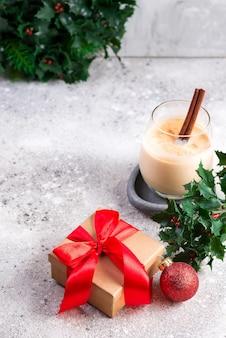 Une boisson chaude épicée d'hiver dans un verre avec cannelle et boîte-cadeau sur une table en pierre claire