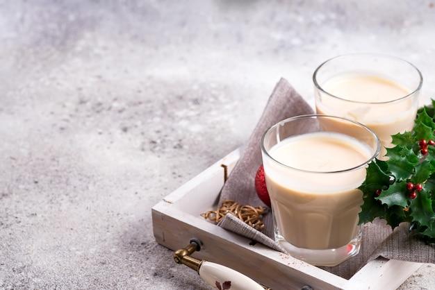 Une boisson chaude épicée en hiver dans un verre à thé de cannelle dans une assiette en pierre, branches de givre sur la table en pierre claire