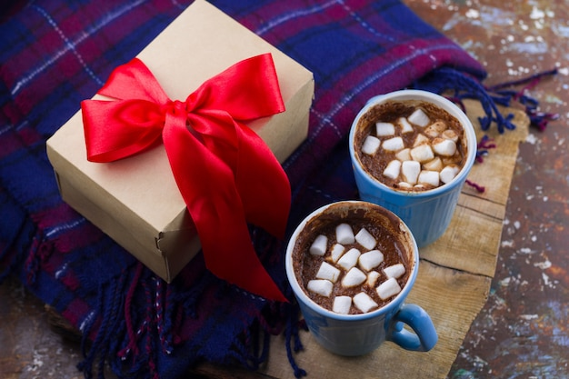 Boisson chaude avec guimauves, plaid et boîte-cadeau avec ruban de satin rouge vue de dessus vacances agréables