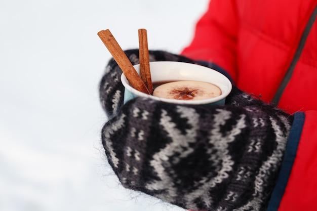 Boisson chaude d'hiver en forêt, vin chaud dans les mains