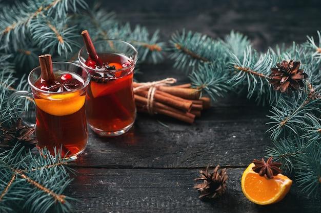Boisson chaude d'hiver vin chaud de noël dans des verres à l'anis, cannelle et mandarine