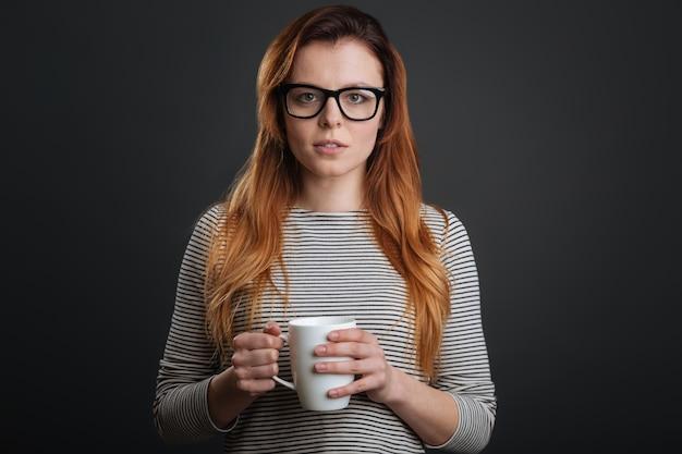 Boisson chaude. jolie jeune femme enchanteresse debout isolée sur fond gris tout en tenant une tasse dans ses mains et portant des lunettes