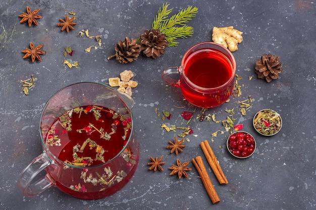 Boisson chaude de noël. thé rouge (rooibos, hibiscus, karkade) dans une tasse en verre et une théière pour la fête de noël parmi les canneberges, l'orange, les cônes, la cannelle. vacances d'hiver, concept de nouvel an. fermer