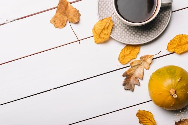 Boisson chaude près des feuilles et de la citrouille