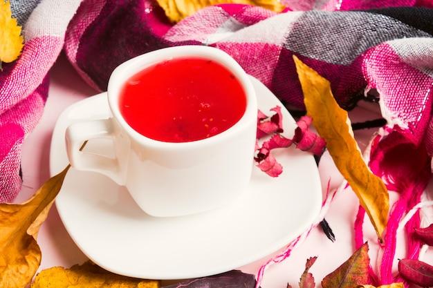 Boisson chaude rouge avec foulard coloré et feuilles sèches