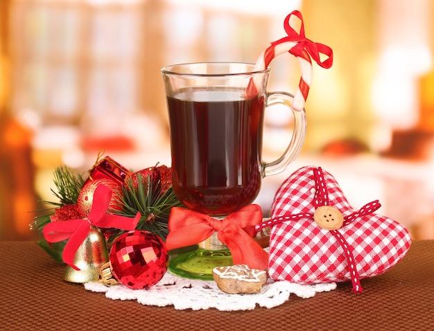 Boisson chaude et savoureuse avec des bonbons de noël et autres décorations sur fond clair