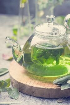 Boisson chaude de thé à la menthe sédative aux herbes dans une théière en verre sur un plateau en bois avec de la menthe fraîche du jardin