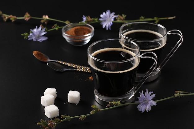 Boisson de chicorée dans deux tasses en verre, avec concentré et fleurs sur fond noir