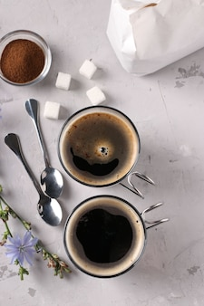 Boisson à la chicorée dans deux tasses en verre, avec concentré et fleurs sur gris
